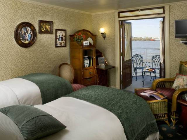 Look right out at Old Man River from your deluxe Outside stateroom with veranda on the American Queen