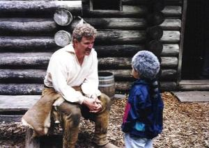 A re-enactor tells a young visitor about life on the Lewis and Clark Expedition, at Fort Clatsop National Park (NPS photo)