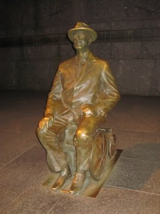 Another realistically sized statue shows FDR's wheelchair. Night time photo by J. Emmons